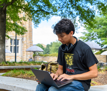 student on laptop in quad