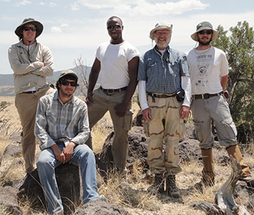 students and faculty smile in the field of a hands-on geology excursion