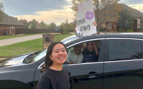 Julianne Tran beside a car in which are two friends holding a happy birthday sign
