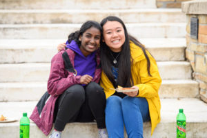 two students sitting together on steps, one with an arm around the other