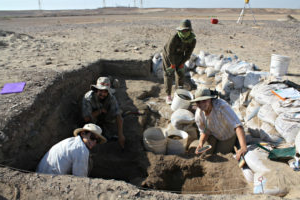 教授达尼埃尔·麦克唐纳 and three other people in an archaeological pit in the 约旦ian desert