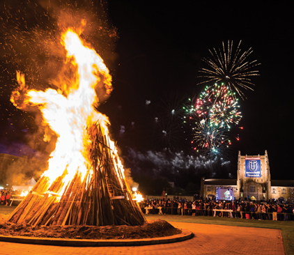 the homecoming bonfire rages as fireworks explode in the sky behind 麦克法林库