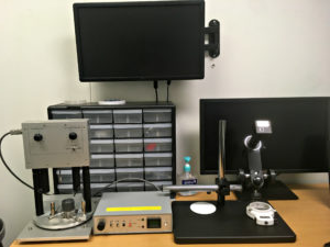 computer monitors, micro-drilling equipment 和 other tools in Professor Zhu's lab