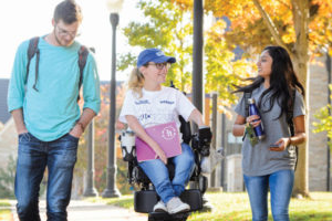 two students walking with a student in a wheelchair