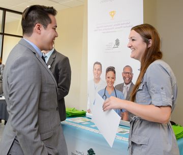 a student speaks with a representative at a job fair