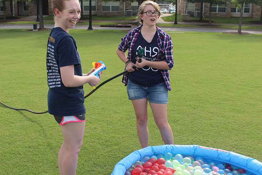 two students fill water balloons