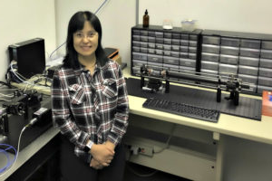 physics professor peifen朱 in her lab with research equipment