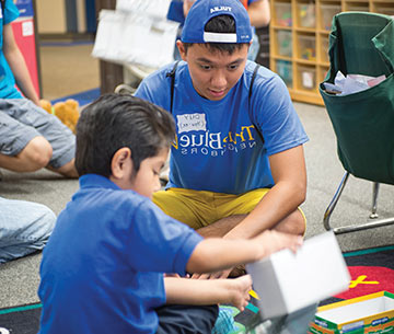 a freshman student plays with a student at Kendall Whittier elementary