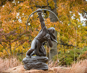 statue of a native American archer in front of fall leaves