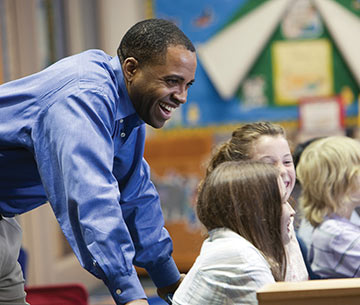 a teacher leans forward behind smiling students